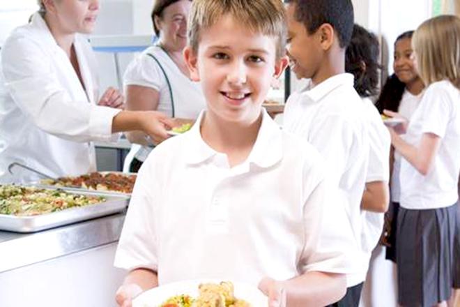 Bé trai cầm đĩa thức ăn