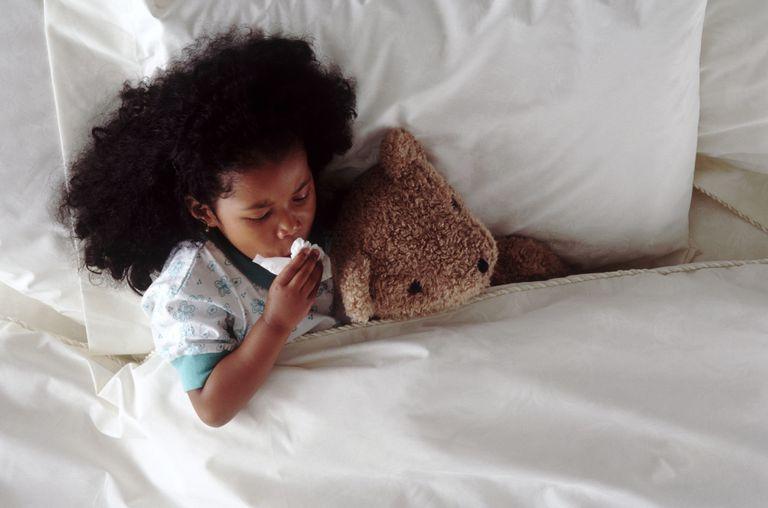 Bé nằm trên giường ho