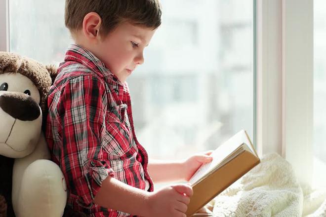 Bé ngồi đọc sách bên cửa sổ đủ ánh sáng
