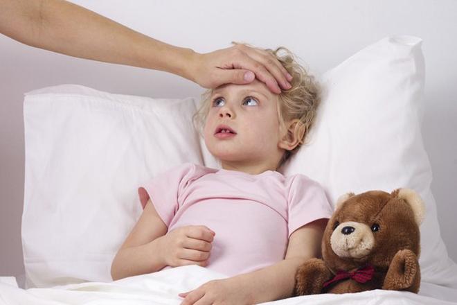 Mẹ rờ đầu bé đang bị sốt