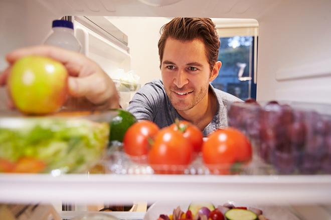 Người đàn ông lấy thực phẩm từ tủ lạnh