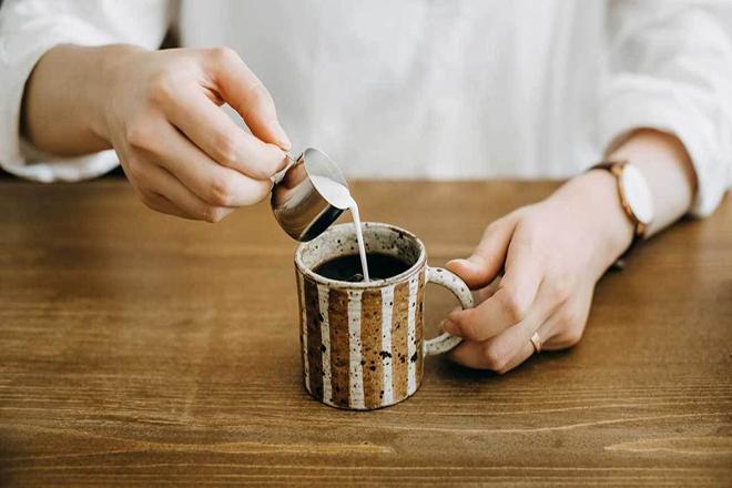 Người đàn ông pha sữa vào cà phê