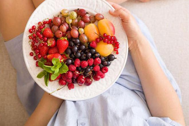 Phụ nữ cầm đĩa trái cây