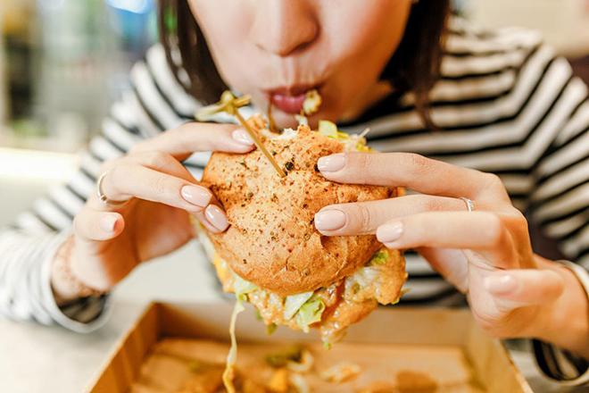 Phụ nữ đang ăn hambuger