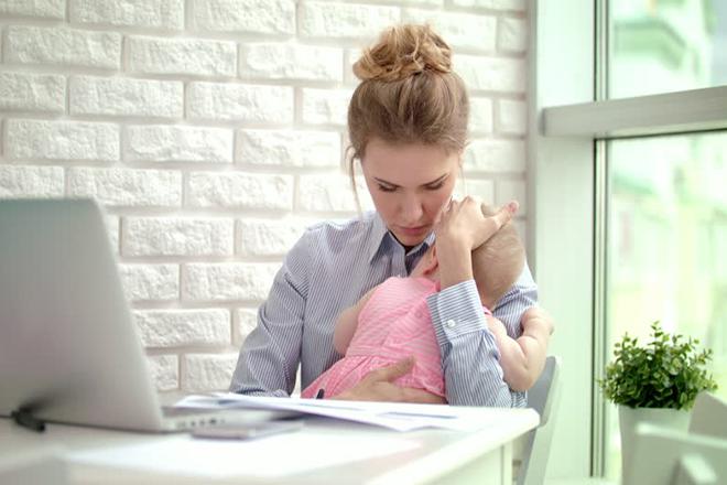 Mẹ vừa ôm con vừa làm việc