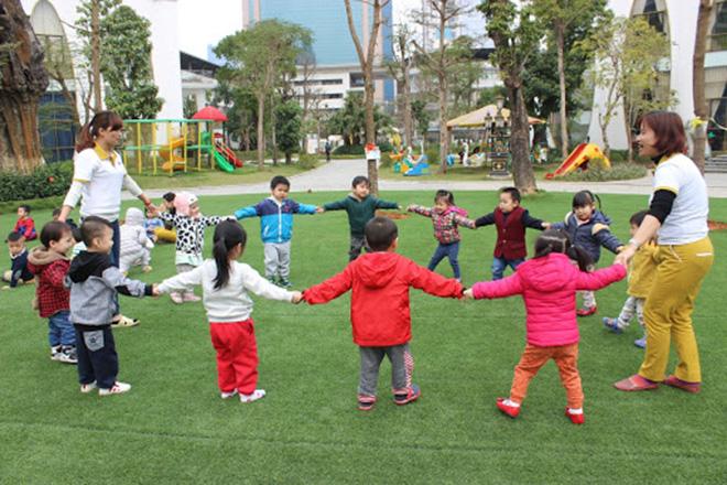 Trẻ chơi cùng cô giáo ngoài trời