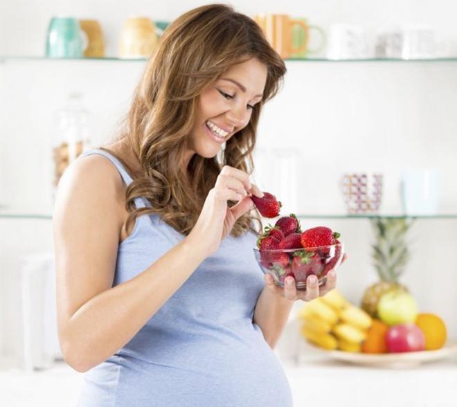 Bà bầu đang cầm tô trái cây