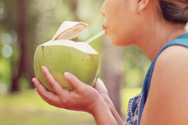 Phụ nữ đang uống trái dừa