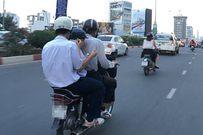 Hai học sinh vừa ngồi trên xe máy vừa tranh thủ ăn cơm hộp